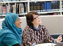 Image of librarian helping a student at the library help desk