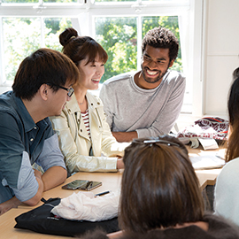 Image of people working together around a table