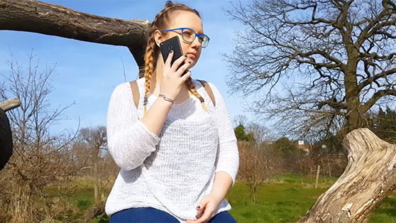 Photo of teenage girl with glasses and plaited pigtails sitting outside with her phone to her ear