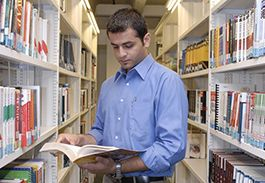 image of person looking at library book shelves