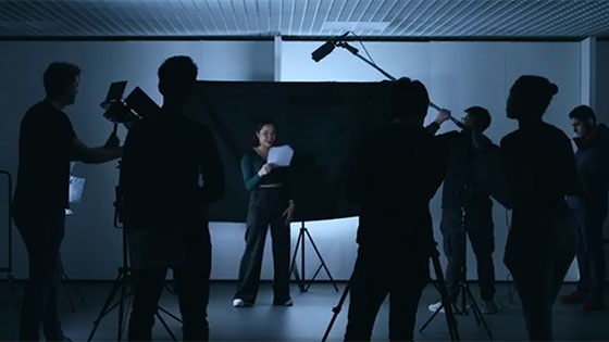 A near silouetted image of a student being filmed reading off a sheet of paper